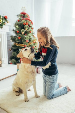 excited kid in warm sweater cuddling labrador and holding present in decorated living room, christmas concept
