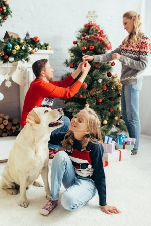 selective focus of kid in sweater cuddling labrador near parents decorating christmas tree in living room