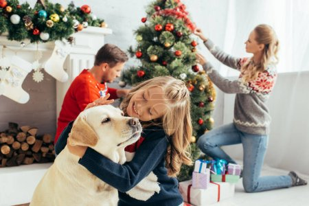 selective focus of happy kid in sweater cuddling labrador near parents decorating christmas tree in living room