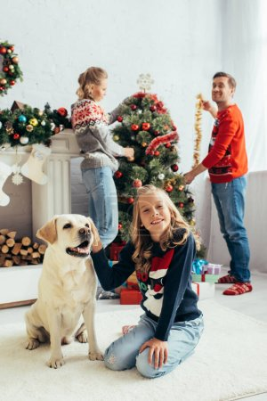 selective focus of joyful girl in sweater cuddling labrador near happy parents decorating christmas tree in living room