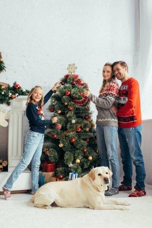 joyful family decorating christmas tree near dog in living room