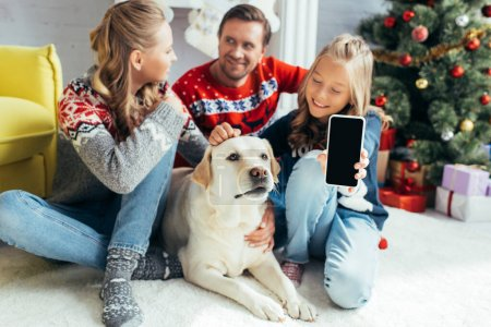 Photo for Joyful kid cuddling dog while holding smartphone with blank screen near parents in decorated living room - Royalty Free Image