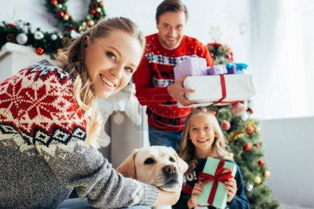 foyer sélectif de femme heureuse câlins chien près de la fille et le mari avec des cadeaux sur Noël