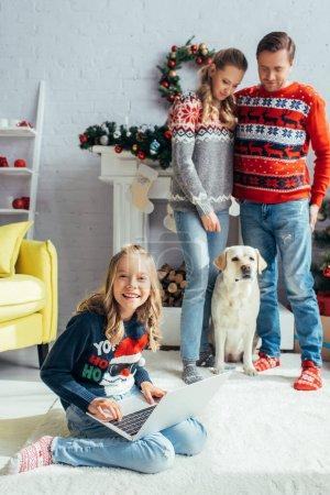 happy kid using laptop near joyful parents standing near dog on christmas