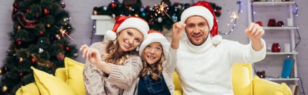 Photo for Happy family in santa hats holding sparklers in decorated living room, banner - Royalty Free Image