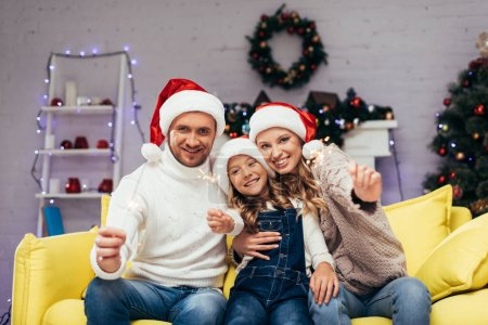 Photo for Happy family in santa hats holding sparklers in decorated living room on christmas - Royalty Free Image