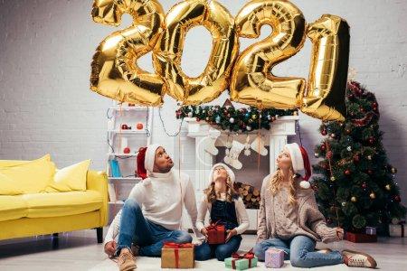 Foto de Familia sorprendida en sombreros de santa sentado cerca de regalos y globos brillantes con números 2021 - Imagen libre de derechos