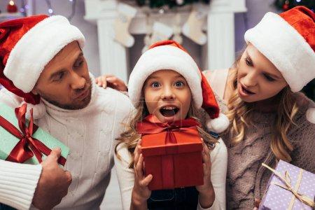 enfant choqué tenant Noël présent près des parents