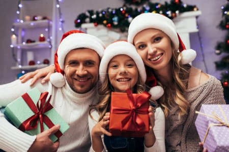 Photo for Happy kid in santa hat holding christmas present near parents - Royalty Free Image