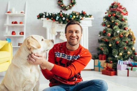 Photo pour Homme gai en pull rouge câlin labrador près de l'arbre de Noël - image libre de droit