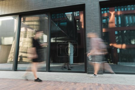 Photo for Motion blur of citizens walking on modern street near building - Royalty Free Image