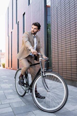 Photo pour Toute la longueur de l'homme barbu en costume à vélo et regardant loin près du bâtiment - image libre de droit