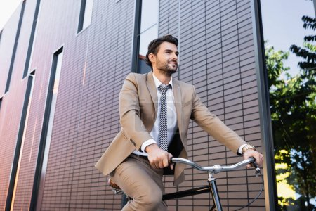 Photo pour Vue à angle bas de l'homme barbu en costume à vélo, souriant et regardant loin près du bâtiment - image libre de droit