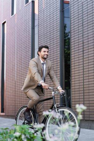 Photo pour Homme heureux en costume à vélo et souriant près du bâtiment et de la plante au premier plan flou - image libre de droit