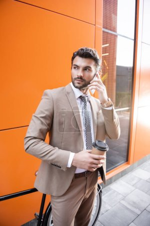 confident businessman talking on smartphone and holding paper cup near bicycle and building with orange walls
