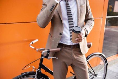 Photo pour Vue partielle d'un homme d'affaires tenant une tasse en papier près d'un vélo et d'un bâtiment aux murs orange - image libre de droit