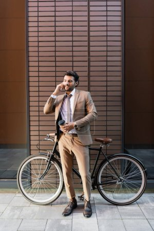 full length of bearded businessman talking on smartphone and holding paper cup near bicycle and modern building