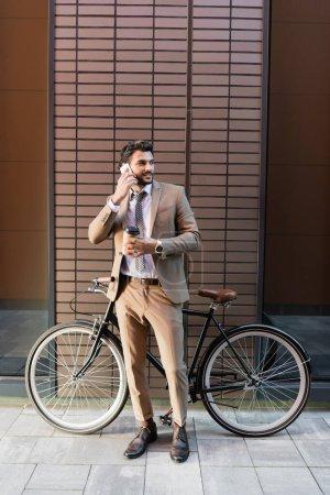 longitud completa de hombre de negocios barbudo hablando en el teléfono inteligente y sosteniendo taza de papel cerca de la bicicleta y la construcción