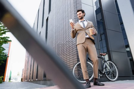 low angle view of cheerful businessman looking at smartphone and holding paper cup near bike and blurred foreground
