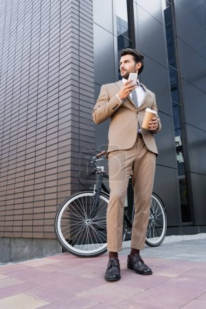 Niederwinkelblick des Geschäftsmannes mit Smartphone und Kaffee in der Nähe von Fahrrad und Gebäude
