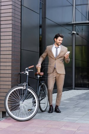 full length of cheerful businessman holding smartphone and coffee to go near bicycle while standing near building