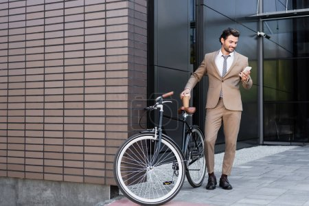 Photo for Full length of smiling businessman holding smartphone and coffee to go near bicycle while standing near building - Royalty Free Image