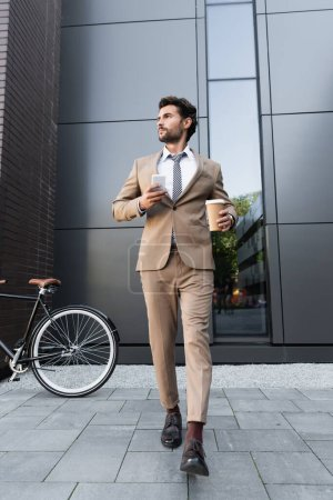 Photo for Full length of businessman in suit holding coffee to go and smartphone while walking near bicycle - Royalty Free Image