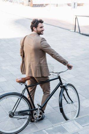 Photo pour Pleine longueur d'homme d'affaires heureux dans les écouteurs sans fil debout près de vélo - image libre de droit