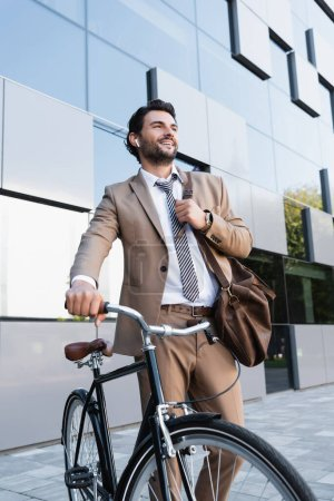 cheerful businessman in wireless earphones while standing with bag near bike and building