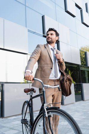 Photo for Businessman in wireless earphones while standing with bag near bike and building - Royalty Free Image