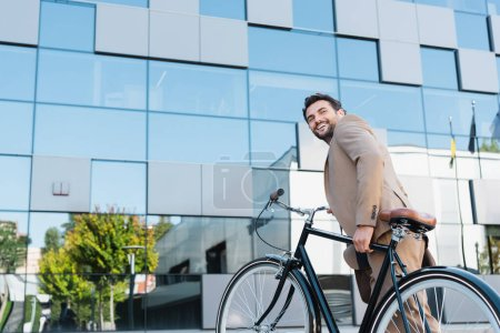 Photo for Happy businessman in wireless earphones walking on stairs with bicycle - Royalty Free Image