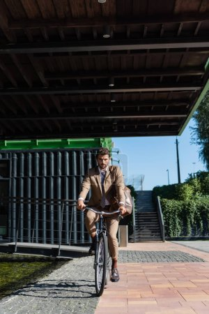 full length of businessman in wireless earphones riding bicycle