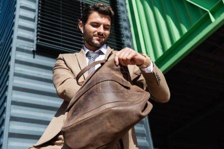 Foto de Vista de ángulo bajo del hombre de negocios feliz en auriculares inalámbricos que sostienen el bolso de cuero - Imagen libre de derechos