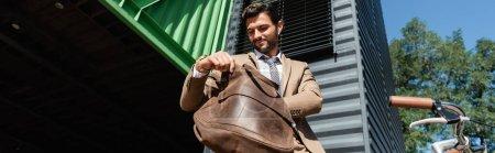 Photo pour Vue à angle bas de l'homme d'affaires heureux dans des écouteurs sans fil tenant sac en cuir, bannière - image libre de droit