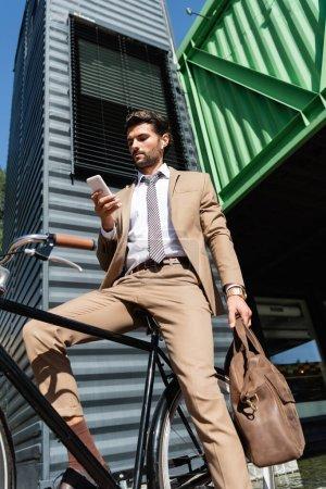 Photo pour Vue à faible angle de l'homme d'affaires barbu dans les écouteurs sans fil debout près du vélo et tenant smartphone - image libre de droit