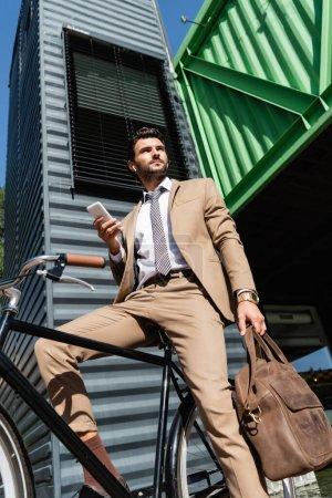 Photo pour Vue à faible angle de l'homme d'affaires dans les écouteurs sans fil debout près de vélo et tenant smartphone - image libre de droit