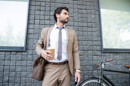 businessman in wireless earphones and suit holding paper cup and smartphone near building