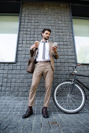 Photo for Full length of businessman in wireless earphones and suit holding paper cup and smartphone near building - Royalty Free Image
