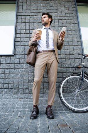 Photo pour Toute la longueur de l'homme d'affaires dans les écouteurs sans fil tenant tasse en papier et smartphone près du bâtiment - image libre de droit