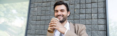 happy businessman in wireless earphones holding paper cup near building, banner