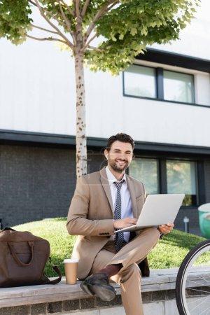 Photo pour Homme d'affaires heureux dans les écouteurs sans fil et costume à l'aide d'un ordinateur portable tout en étant assis sur le banc - image libre de droit