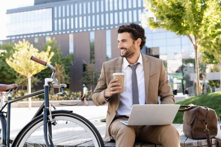 happy businessman in suit using laptop and holding paper cup while sitting on bench near bike