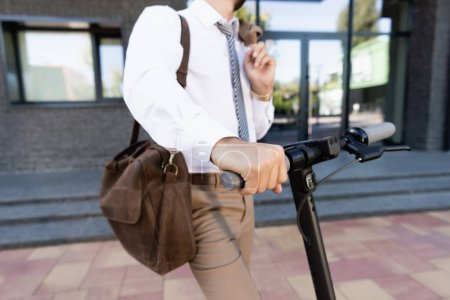 cropped view of businessman in formal wear standing near e-scooter with leather bag on blurred background