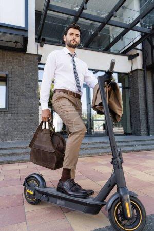 Foto de Longitud completa de hombre de negocios en desgaste formal de pie cerca de e-scooter con bolsa de cuero - Imagen libre de derechos