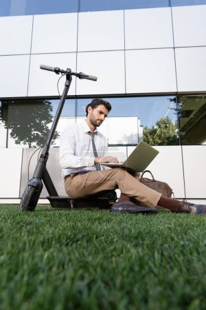 businessman in formal wear sitting with laptop near e-scooter on grass