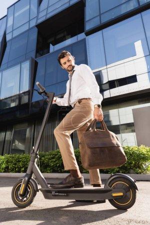 volle Länge des bärtigen Geschäftsmann in formeller Kleidung mit Ledertasche Reiten Elektroroller
