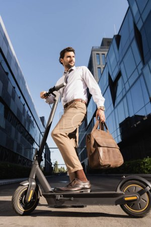 Photo for Low angle view of businessman in formal wear holding leather bag and standing near electric scooter - Royalty Free Image