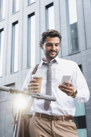 Photo for Smiling businessman in formal wear holding paper cup and using smartphone near e-scooter - Royalty Free Image
