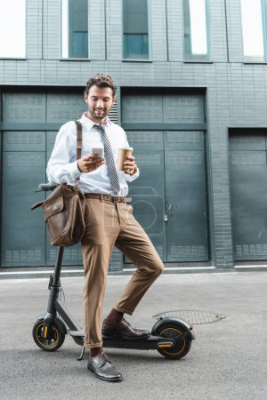 full length of happy businessman in formal wear holding paper cup and texting on  smartphone near e-scooter