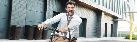 Photo pour Homme d'affaires étonné en tenue formelle équitation scooter électrique, bannière horizontale - image libre de droit